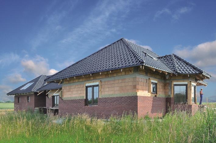 Budowa ściany trójwarstwowej w dwóch etapach - izolację z wełny i elewację układa się dopiero po pokryciu dachu. Fot. Röben