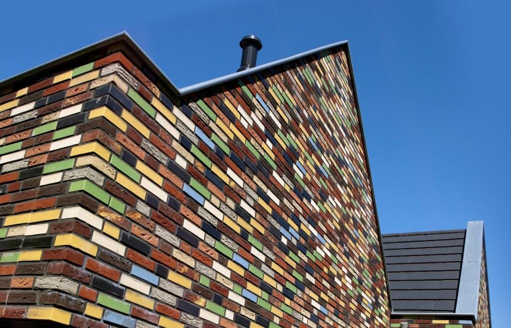 Elewacja z cegieł szkliwionych to wyraz odważnej, modernistycznej architektury stawiającej na lśniące, intensywne barwy i prawdziwy kolaż kolorów. Widoczna na zdjęciu feeria barw szkliwionych cegieł w połączeniu z bardziej stonowanymi cegłami z fakturą żłobioną to prawdziwy majstersztyk wśród elewacji. Zorgwoningen, Austria. Fot. Wienerberger