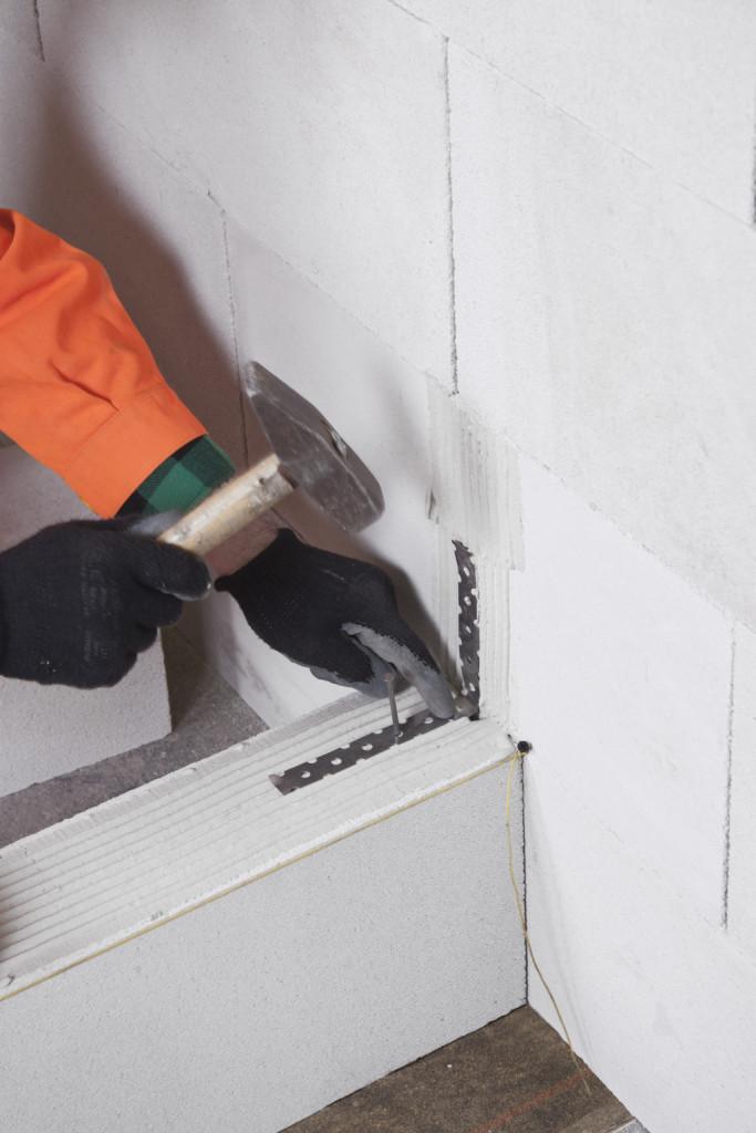 """Łączenie ścianki działowej ze ścianą nośną. Metalowe kotwy wygięte w kształt litery """"L"""" możemy przybijać do bloczków gwoździami lub kołkami rozporowymi. Fot. BRUK-BET"""