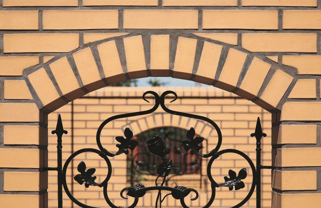 Elegancja z nutą romantyzmu: cegła klinkierowa Sahara to ciekawy pomysł na materiał do budowy ogrodzenia, zwłaszcza w połączeniu ze stylowymi elementami kutymi. Fot. CRH Klinkier